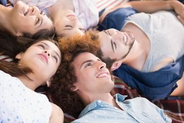 Happy friends lying on blanket