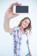 Pretty hipster taking selfie with smartphone