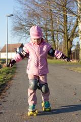 kleines Mädchen lernt Rollschuhfahren