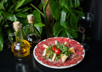white dish with carpaccio of beef on black table