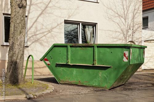 ein gr ner container f r abfall steht vor einem wohnhaus stockfotos und lizenzfreie bilder auf. Black Bedroom Furniture Sets. Home Design Ideas