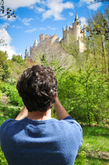 young traveler taking pictures of a castle in segovia spain