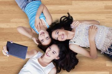 Teenage girls lying down and taking photo