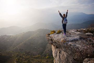Young woman standing on cliff with outstretched arms