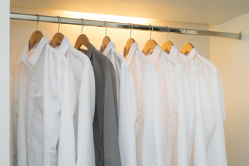 row of white and grey shirts hanging on coat hanger in white war