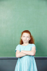 Girl in front of chalkboard in school