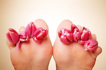 Füße mit roten Tulpen vor beigen Hintergrund