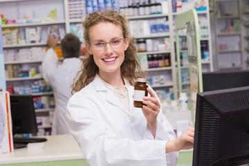 Pharmacist holding medicine bottle
