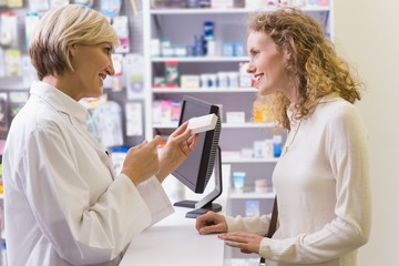 Pharmacist holding medicine box talking to customer