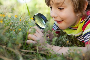 Happy little boy looking through magnifying glass