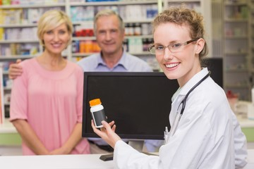 Pharmacist showing medicine jar to a customer