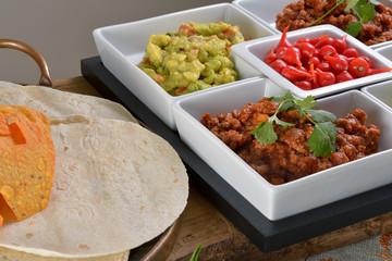 Mexican food - chilli, guacamole, tortillas and nachos