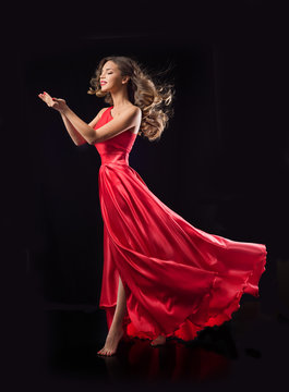 Young beauty woman in red waving flying  dress. Dancer in silk d