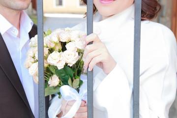 bride and groom behind bars