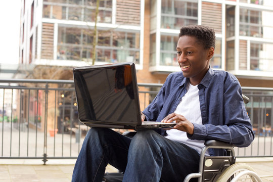 a young wheelchair user working on a laptop.