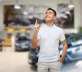 smiling man pointing finger up over auto show