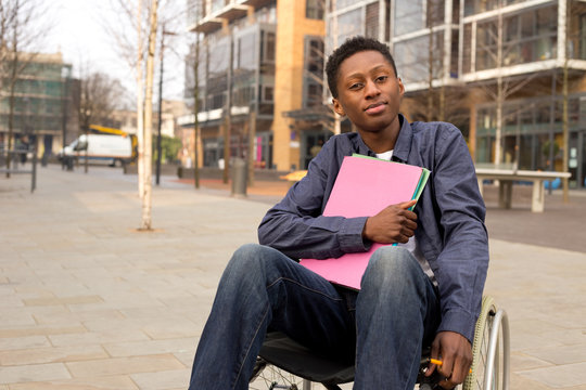 young disabled student sitting in a wheelchair  holding folders