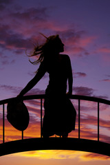 silhouette of a woman in a skirt hold hat down hair blowing