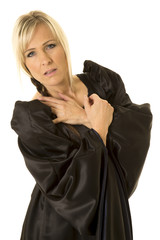 woman in black cloak arms crossed on chest looking