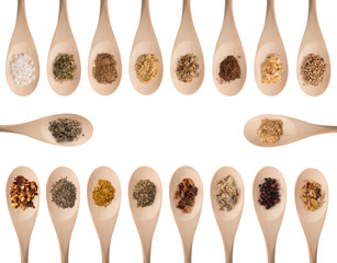Various spices on wooden spoons isolated on white