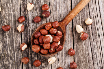 Hazelnuts on a spoon on wooden background.