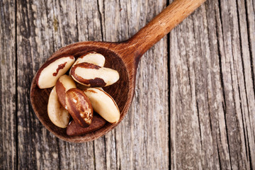 Brazil nuts on a spoon on wooden background.