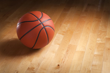 Basketball on hardwood court floor with spot lighting