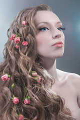 Beauty portrait with red roses in hair