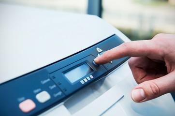 Finger on start button of laser printer