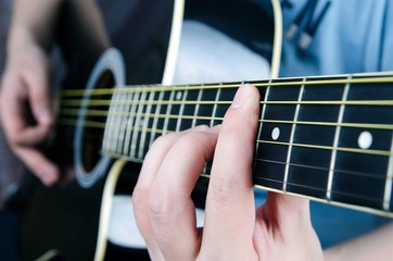 Close up of playing guitar. Musician holding a chord