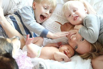 Happy Young Mother and Three Children Snuggling on Bed