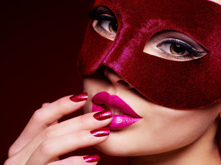 Beautiful  woman with red nails and red theatre mask on face.