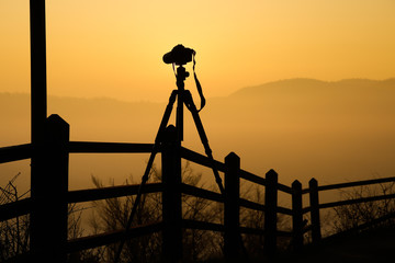 Silhouette of tripod with camera