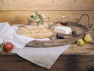 Fresh bread and fruit on wooden tray on table
