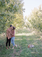 An apple orchard in Utah. A couple kissing.