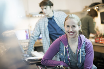 A young woman and man, staff in a computer repair shop.