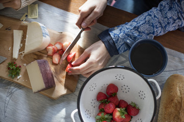 A woman slicing strawberries on a table with a wooden chopping board with a selection of cheeses and bread.