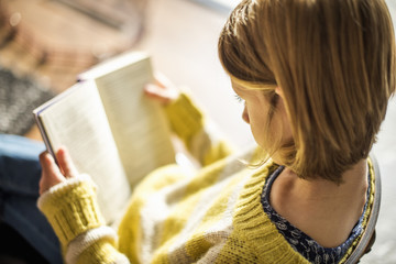 High angle view of a blond girl in a yellow jumper sitting on a chair, reading a book.