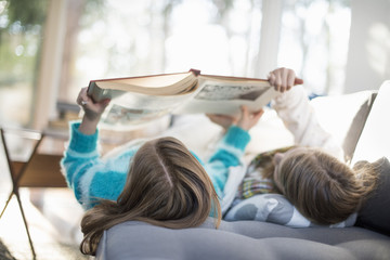 Two girls lying on a sofa on their back, reading a book.