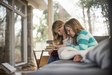 Two girls sitting on a sofa, reading a book.
