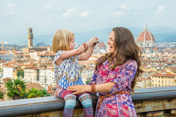Happy baby girl taking photo of mother  in  florence