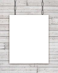 White rectangular poster hanging on chain over wooden background