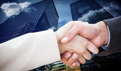 Composite image of close up on partners shaking hands
