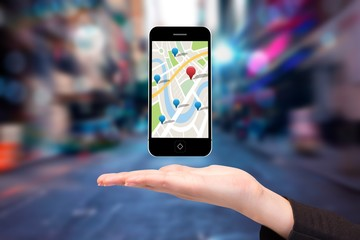 Composite image of hand showing map app on phone