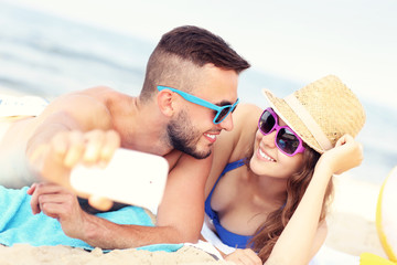 Young couple taking selfie at the beach