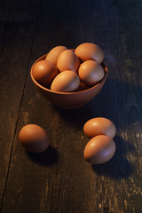 chicken eggs on a dark wooden background