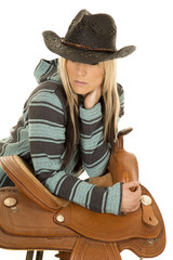 cowgirl in blue and black poncho lean on saddle look down