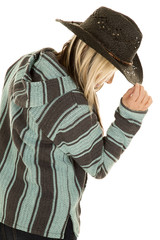 cowgirl in blue and black poncho side lean down