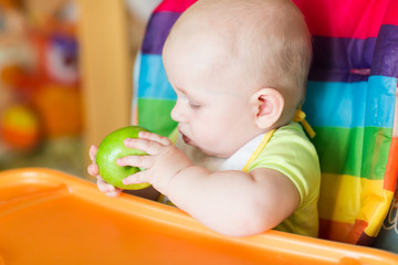 Adorable baby eating apple in high chair