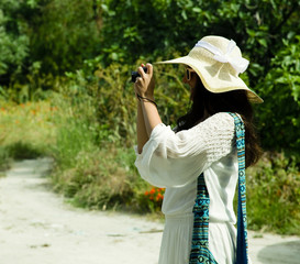 young woman photographer taking photo, summer day
